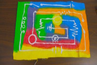Activity for children uses glue batik on fabric to show how silicon chips are made. Includes electric circuit diagrams for grades 4-12.