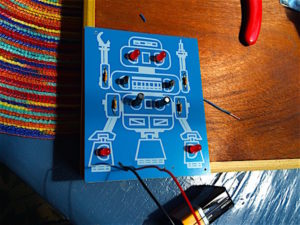 Learn to solder activity for practicing engineering electronics skill for a blinking robot circuit board with LEDs, resistors, and capacitors.
